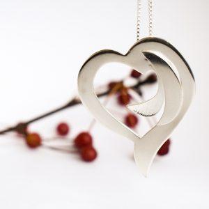 Rosoinen sydänriipus, joka on designattu hopealevystä.