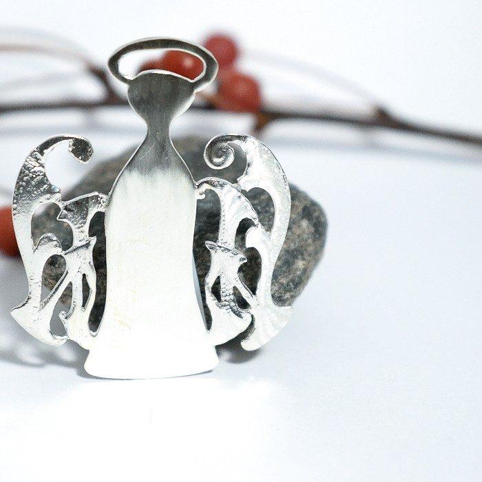 Pitsienkeli-rintaneula, joka muotoiltu hopealevystä ja johon on yhdistetty vanha koru siiviksi.