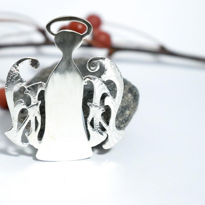 Pitsienkeli-rintaneula, joka on muotoiltu hopealevystä. Hopealevy on valmistettu lusikanosista sulatetusta hopeasta. Enkelin siivet on muotoiltu vanhasta hopeakorusta.
