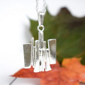 Jääpuikot-riipus, joka on muotoiltu hopealusikoiden varsista.