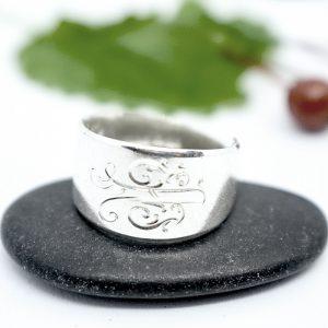 Lusikan varresta tehty hopeasormus, jossa kiekurainen monogrammi.