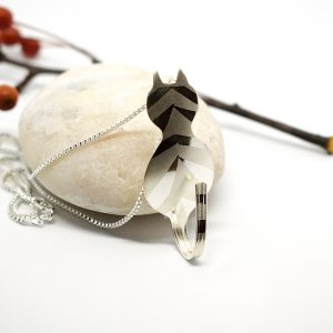 Raitakissa-riipus, joka on muotoiltu hopeisesta kahvilusikasta. Kissa on designattu lusikanpesästä, häntänä lusikan varsi, raidat hiekkapuhallettu.