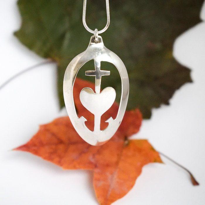 Usko-Toivo-Rakkaus-riipus, joka on designattu hopeiseen lusikanpesään.