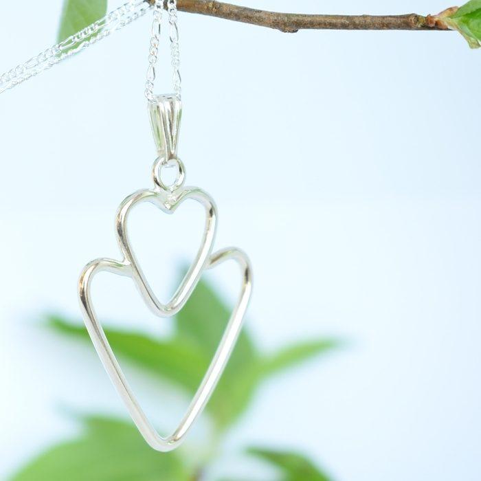 Tuplasydän-riipus, jossa Sterling-hopealangasta muotoiltu kaksi sydäntä päällekkäin.