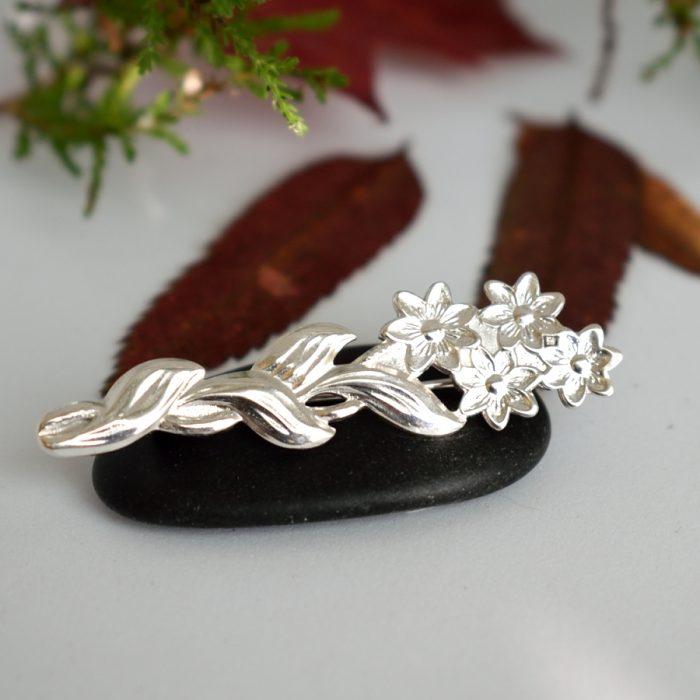 Kukkaset-rintaneula, joka valmistettu hopealusikan varresta.
