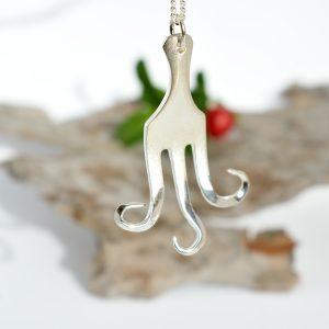 Mustekala-riipus, joka on muotoiltu hopeisesta leikkelehaarukasta.