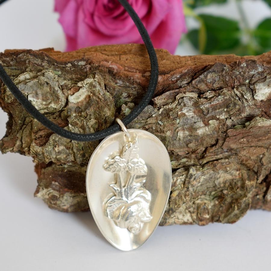 Auranruusu-riipus, joka designattu hopeisesta lusikanpesästä, johon juotettu varren ruusu koristeeksi.
