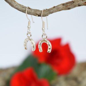 Hevosenkenkä-korvakorut, jotka on muotoiltu hopealusikoiden ohuista varsiosista.