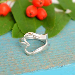 Sydän-haarukkasormus, joka on muotoiltu pienestä, hopeisesta leikkelehaarukasta.