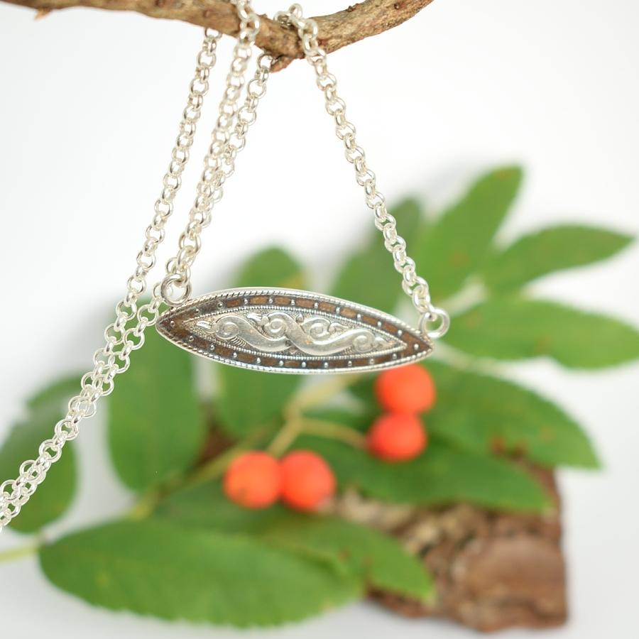 Käärmeet-laattariipus, joka on designattu hopealusikan varresta.