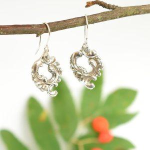 Seppele-korvakorut, jotka ovat roikkuvat korvakorut ja jotka on designattu hopeisten kahvilusikoiden varsien renkuloista.
