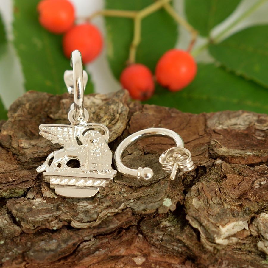 Siivekäs-leijona-korvakoru, joka on designattu hopeisen italialaisen matkamuistolusikan varresta. Toinen korvakoru pelkkä hopearengas, koruissa tappikiinnitys.