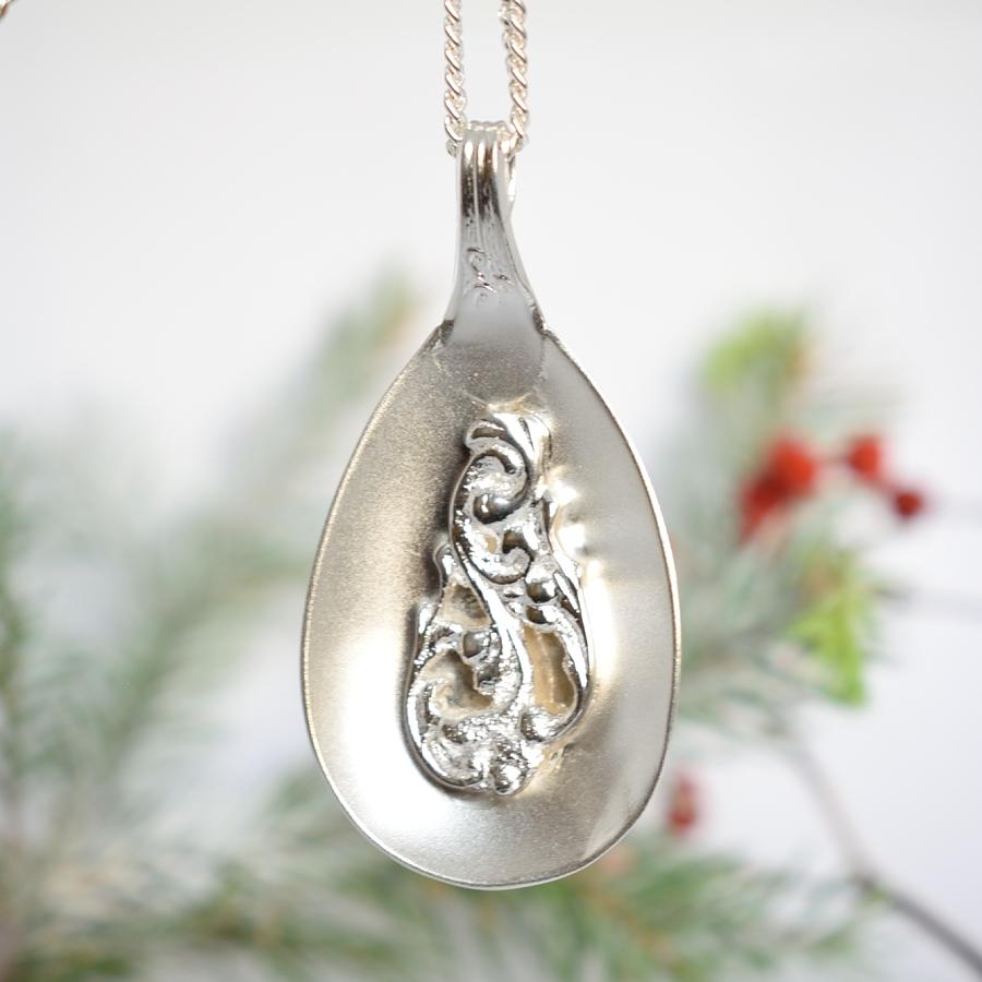Ramona-riipus, joka on valmistettu hopeisen hillolusikan pesästä, johon on juotettu saman lusikan varren pää.