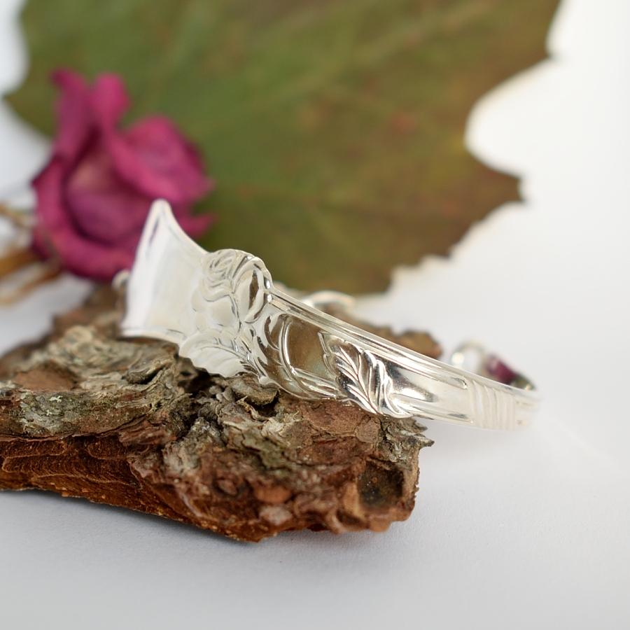 Ruusu-rannekoru, joka on muotoiltu hopeisen jälkiruokalusikan varsiosasta. Korua täydennetty käsin punotulla ketjulla.