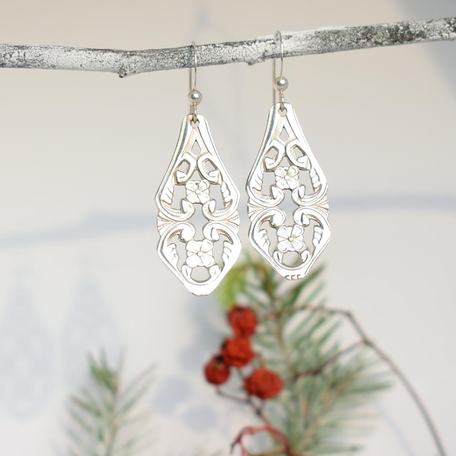 Taika-korvakorut, jotka on valmistettu hopeisten, norjalaisten kahvilusikoiden varsien päistä.