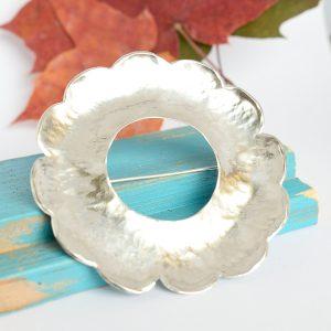 Kukka-rintaneula, joka valmistettu hopeisen perunalusikan pesästä.