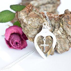 Rakkauden-voima-riipukseen on hopeiseen lusikanpesään muotoiltu sydän, johon on kiinnitetty riippumaan pieni risti.