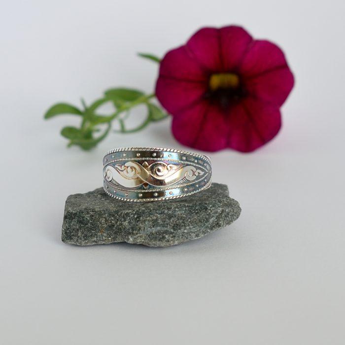 Käärmeet-sormus, joka on valmistettu hopeisesta kuviollisesta kahvilusikasta. Sormuksen kuviopintaan on lisätty tummennusta.