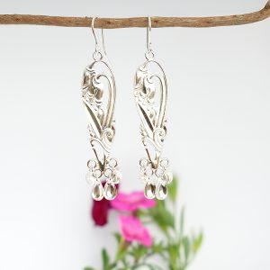Lapinkello-korvakorut on muotoiltu hopeisten kahvilusikoiden varsista ja korujen alaosaan on lappilaisten korujen tyyliin kiinnitetty hopeisia laukkasia.