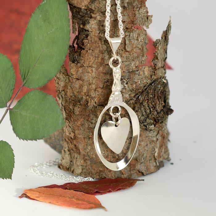 Julia-riipus, joka on muotoiltu pienen, hopeisen mokkalusikan pesästä, josta riippuu irrallinen sydän.
