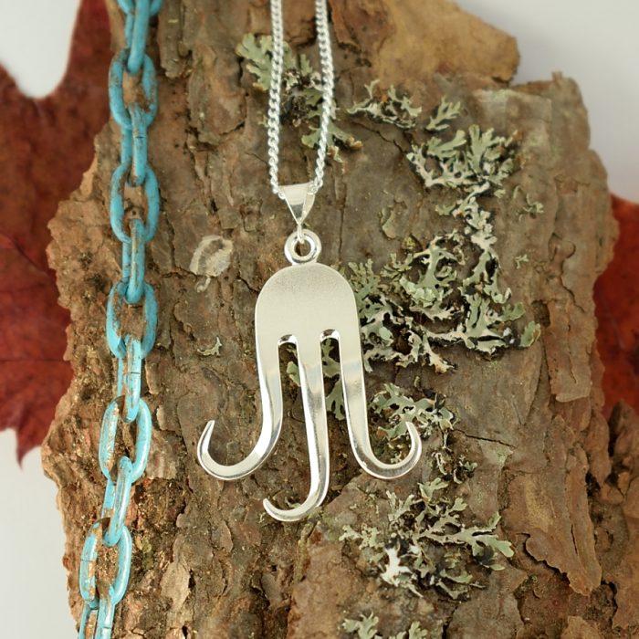 Kalmari-riipus, joka on muotoiltu pienestä kolmepiikkisestä hopeisesta haarukasta.