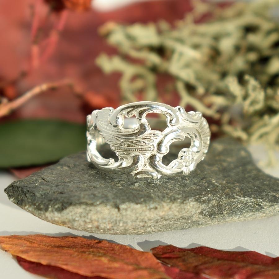 Runo-sormus, joka on muotoiltu hopeisen, koristeellisen lusikan varresta.