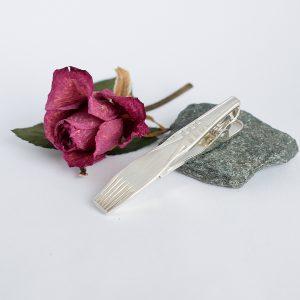 Suomi-solmioneula on muotoiltu hopeisen Suomi-kahvilusikan varsiosasta.