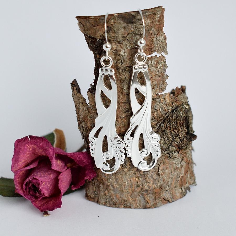 Helmi-korvakorut, jotka on valmistettu hopeisten, koristeellisten lusikoiden varsista.