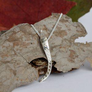 Käärme-riipus, joka on muotoiltu hopeisen keilapalkintolusikan varresta.