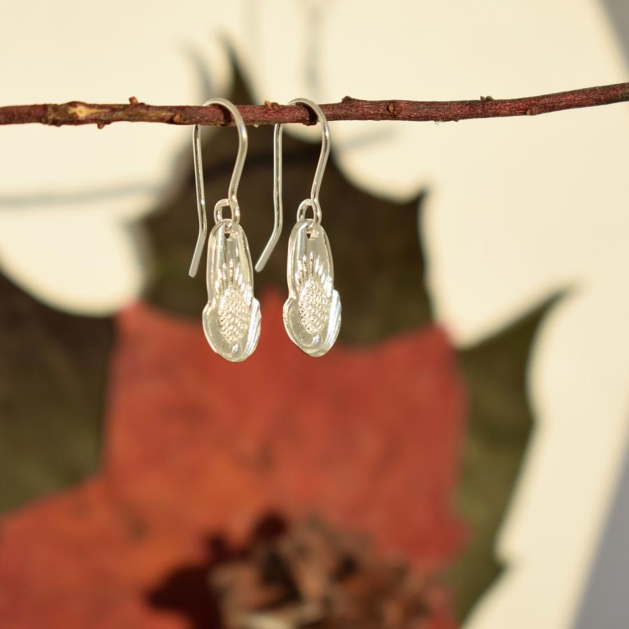 Käpynen-korvakorut, jotka on valmistettu hopeisten kahvilusikoiden varsien päistä.