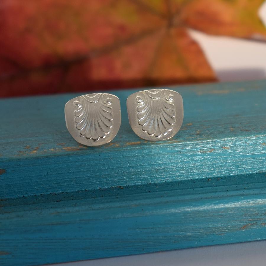 Simpukka-korvakorut, jotka on valmistettu hopeisten Musla-mokkalusikoiden varsien päistä.