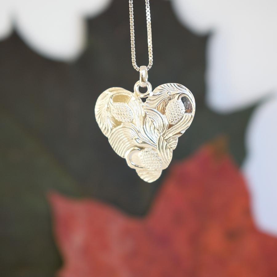 Sydänkäpy-riipus, joka on muotoiltu hopeisten kahvilusikoiden varsista.