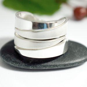 Haarukat-sormus, joka on muotoiltu kahdesta hopeahaarukasta. Sormuksen keskiosa on matattu hiekkapuhaltamalla ja reunaosat ovat kiiltäväpintaiset.