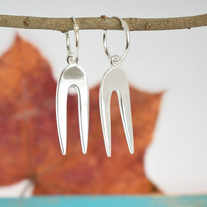Asenne-korvakorut, jotka on valmistettu pienistä, hopeisista leikkelehaarukoista.