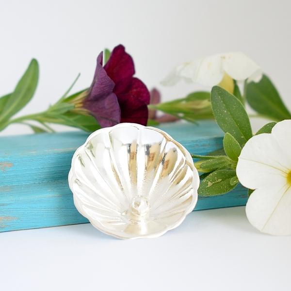 Helmisimpukka-rintaneula, joka on valmistettu hopeisen sokerilusikan pesästä. Pesään on juotettu hopeahelmi.