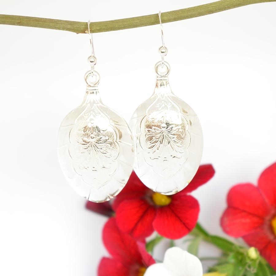 Lehdykät-korvakorut, jotka on valmistettu hopeisten, suomalaisten mokkalusikoiden pesistä. Pesissä on kaunis lehtikuviointi.