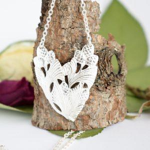 Sydänkäpy-riipus, joka on muotoiltu hopeisten Käpy-lusikoiden varsista sydämen muotoiseksi.